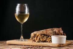 南瓜松饼和被烘烤的肉卷与填装,与一个调味汁一起在一块木板材和一杯白葡萄酒在一黑backgro 免版税图库摄影