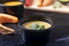 南瓜汤和薄荷叶、匙子、胡椒和豌豆粥在食盒在木桌,被弄脏的bacground上 库存图片