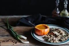 南瓜汤在南瓜和蘑菇服务在喜怒无常的板材黑暗和 库存照片