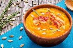 南瓜汤用烟肉,南瓜籽和rozemary在弓 图库摄影