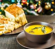 南瓜汤用贤哲在棕色陶瓷汤盘离开与蒜味面包在圣诞树附近 免版税库存图片