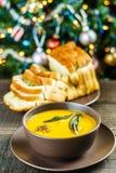 南瓜汤用贤哲在棕色陶瓷汤盘离开与蒜味面包在圣诞树附近 库存照片