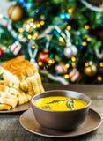 南瓜汤用贤哲在棕色陶瓷汤盘离开与蒜味面包在圣诞树附近 图库摄影