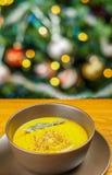 南瓜汤用贤哲在棕色陶瓷汤盘离开在圣诞树附近 免版税库存照片