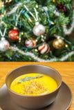 南瓜汤用贤哲在棕色陶瓷汤盘离开在圣诞树附近 库存照片