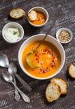南瓜汤用辣椒粉、亚麻籽和奶油在一个白色碗 库存照片