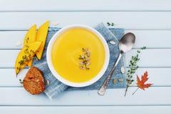 南瓜汤装饰了种子和麝香草在白色碗在蓝色台式视图 平位置称呼 免版税库存图片
