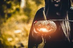 南瓜灯笼在巫婆手上 老妇人在黑暗的藏品南瓜 免版税库存照片