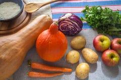 南瓜用红萝卜、土豆、圆白菜、苹果、新鲜的沙拉和米在一张木桌上 库存照片