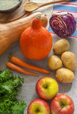南瓜用红萝卜、土豆、圆白菜、苹果、新鲜的沙拉和米在一张木桌上 免版税库存照片
