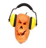 南瓜的可怕邪恶的面孔与耳机的。 免版税图库摄影
