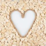 南瓜籽和一条绳索以心脏的形式与一个地方设计师的 库存照片
