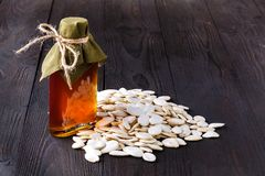 南瓜籽和在桌,在一个玻璃瓶子的处女南瓜油上 库存照片