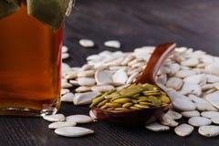 南瓜籽和在桌,在一个玻璃瓶子的处女南瓜油上 免版税库存图片