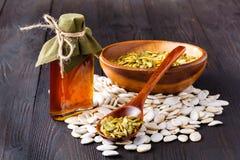 南瓜籽和在桌,在一个玻璃瓶子的处女南瓜油上 图库摄影