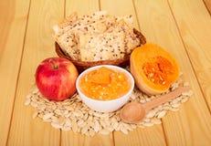 南瓜籽,碗纯汁浓汤,饼干,在背景光木头的苹果 图库摄影