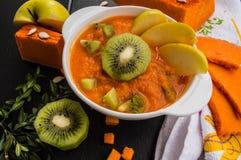 南瓜纯汁浓汤清淡的早餐用在黑木背景的果子 顶视图 特写镜头 库存图片