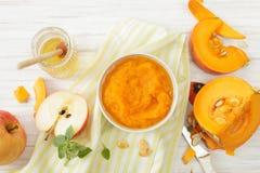 南瓜纯汁浓汤用蜂蜜、苹果计算机和桂香在白色桌上 库存照片