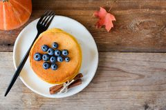 南瓜薄煎饼冠上了用在木背景的新鲜的蓝莓 库存照片