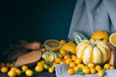 南瓜,金桔,桔子,白薯,红萝卜,在黑暗的木背景的秋天构成,定了调子图片 免版税库存照片