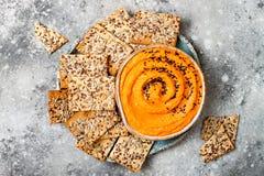 南瓜hummus用橄榄油和黑芝麻籽晒干了用整个五谷薄脆饼干 健康素食开胃菜或快餐 库存照片