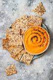 南瓜hummus用橄榄油和黑芝麻籽晒干了用整个五谷薄脆饼干 健康素食开胃菜或快餐 免版税库存照片
