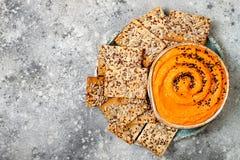 南瓜hummus用橄榄油和黑芝麻籽晒干了用整个五谷薄脆饼干 健康素食开胃菜或快餐 免版税库存图片