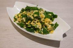南部的泰国菜混乱油煎了用在白色板材的鸡蛋 免版税库存图片