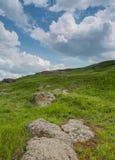 南部的臭虫河的岩石岸 绿草和红色石头在岸反对蓝天 免版税库存照片