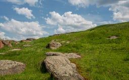南部的臭虫河的岩石岸 绿草和红色石头在岸反对蓝天 免版税库存图片