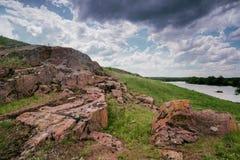 南部的臭虫河的岩石岸 绿草和红色石头在岸反对蓝天 库存图片