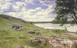 南部的臭虫河的岩石岸 绿草和红色石头在岸反对蓝天 图库摄影