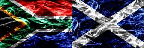 南非对苏格兰,肩并肩被安置的苏格兰烟旗子 概念和想法旗子混合 库存照片