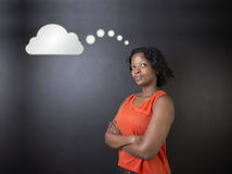 南非或非裔美国人的妇女老师或学生认为云彩 免版税库存照片