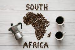 南非的地图放置在与coffe制造商,咖啡的白色木织地不很细背景的由烤咖啡豆制成 免版税库存照片
