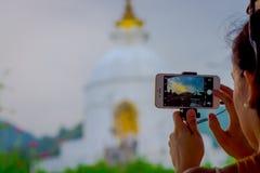 博克拉,尼泊尔, 2017年9月04日:关闭寺庙的美丽的景色在一个智能手机的屏幕的有a的 免版税库存图片