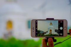 博克拉,尼泊尔, 2017年9月04日:关闭寺庙的美丽的景色在一个智能手机的屏幕的有a的 免版税图库摄影