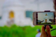 博克拉,尼泊尔, 2017年9月04日:关闭寺庙的美丽的景色在一个智能手机的屏幕的有a的 免版税库存照片