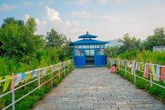 博克拉,尼泊尔, 2017年9月04日:关闭有一个蓝色小屋的一条扔石头的道路接近Phewa Tal,精采白 免版税库存照片