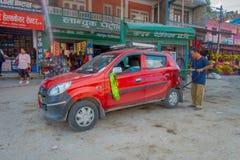 博克拉,尼泊尔, 2017年9月04日:加油站的未认出的人与他的红色汽车在dowtown停放了在博克拉附近 免版税库存图片