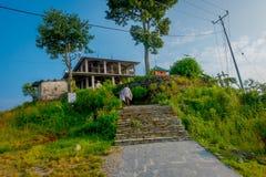 博克拉,尼泊尔, 2017年9月04日:走到他们的路线的房子的未认出的人民在Sarangkot山,尼泊尔 免版税库存照片