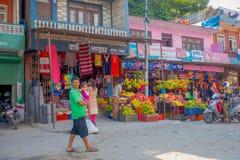博克拉,尼泊尔, 2017年9月04日:走在街道在dowtown的食物市场户外的未认出的人民在附近 库存图片