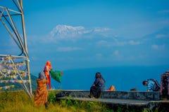 博克拉,尼泊尔, 2017年9月04日:Sarangkot监视的小山顶的未认出的游人指向,拿着旗子和 库存照片