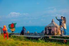 博克拉,尼泊尔, 2017年9月04日:Sarangkot监视的小山顶的未认出的游人指向,拿着旗子和 免版税库存图片