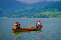 博克拉,尼泊尔- 2017年11月04日:享受与旅游指南的未认出的夫妇看法用浆划在的小船 免版税库存图片