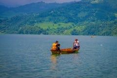 博克拉,尼泊尔- 2017年11月04日:享受与旅游指南的未认出的夫妇看法用浆划在的小船 库存照片
