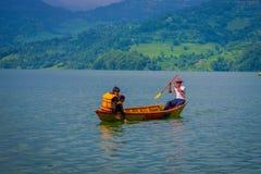 博克拉,尼泊尔- 2017年11月04日:享受与旅游指南的未认出的夫妇看法用浆划在的小船 图库摄影
