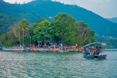 博克拉,尼泊尔- 2017年9月04日:享受在一条小船的未认出的人民一次旅行在有海岛的Phewa tal湖 图库摄影