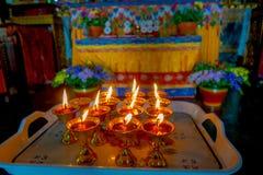 博克拉,尼泊尔- 2017年10月06日:关闭在一个觚里面的一些candels在塑料盘子在Thrangu塔石 免版税库存照片