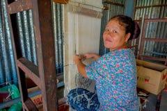博克拉,尼泊尔- 2017年10月06日:关闭工作在织布机制造业羊毛披肩的未认出的微笑的妇女 图库摄影